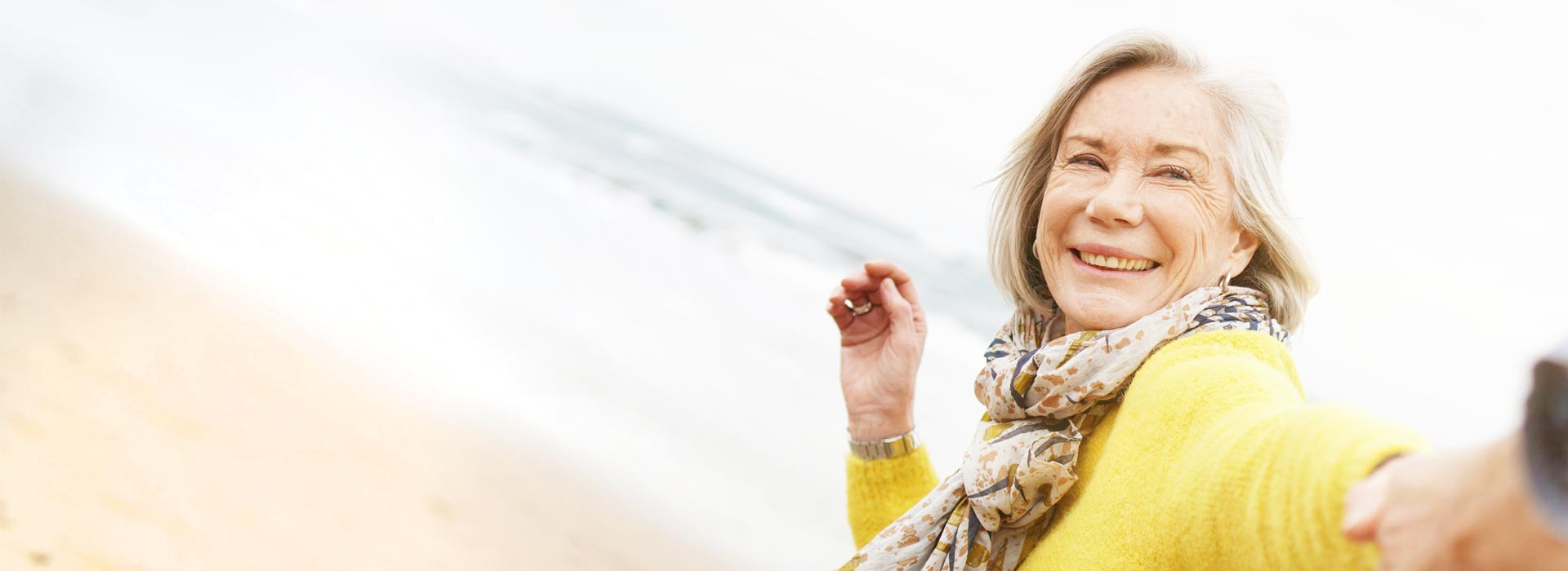 A beautiful senior woman is smiling at the beach